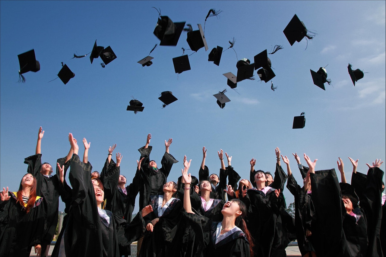 students wearing graduation uniforms with blue clear sky